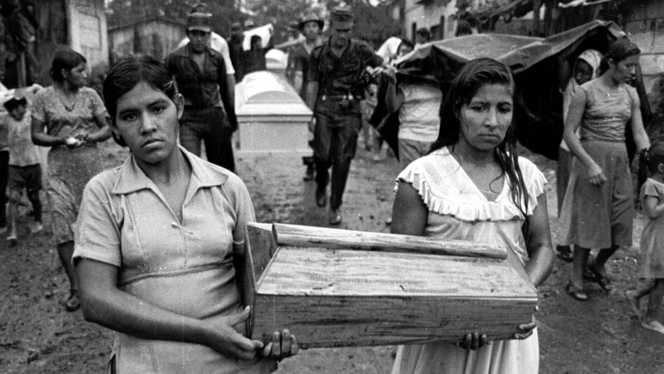 Two young women carry a small coffin between them. Black and white photo.