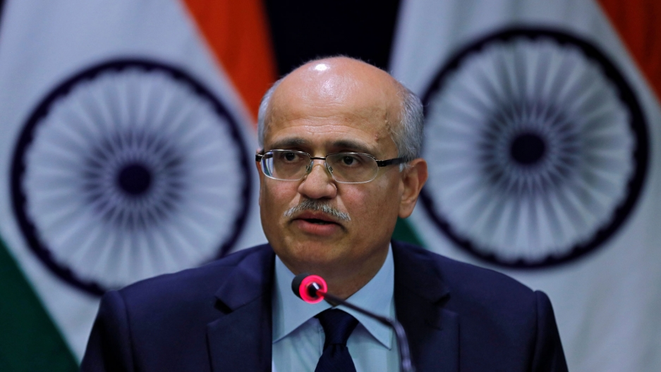 India's Foreign Secretary Vijay Gokhale is shown wearing a blue suit and speaking into a microphone with Indian flags behind him.