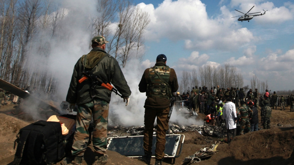 Indian soldiers stand next to the wreckage of Indian Air Force's helicopter