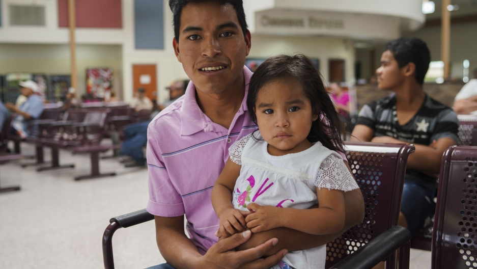 A portrait of a father wearing a pink shirt and his infant daughter who is wearing white.