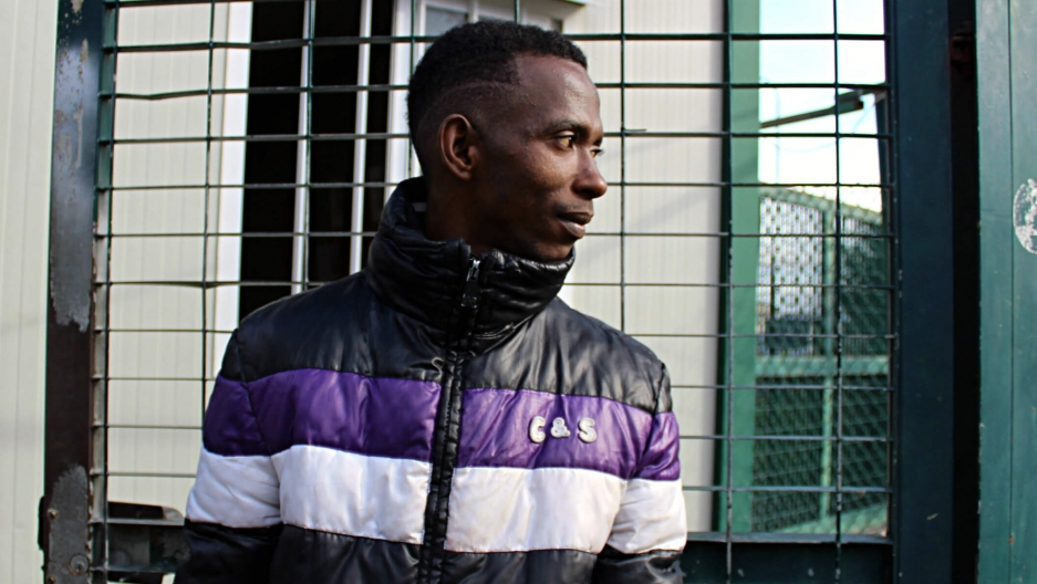 A young African man wearing a purple and white jacket stands and looks to the left.