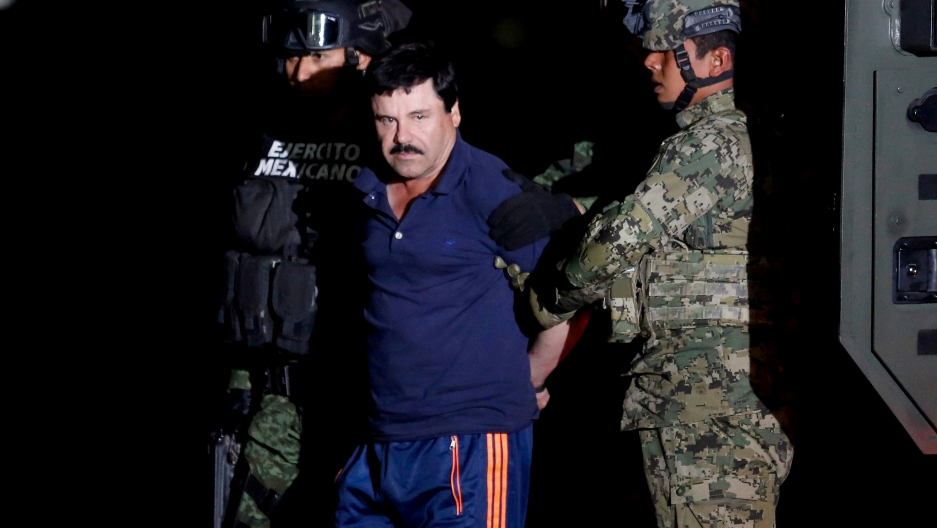 """El Chapo"" in blue uniform stands near police."