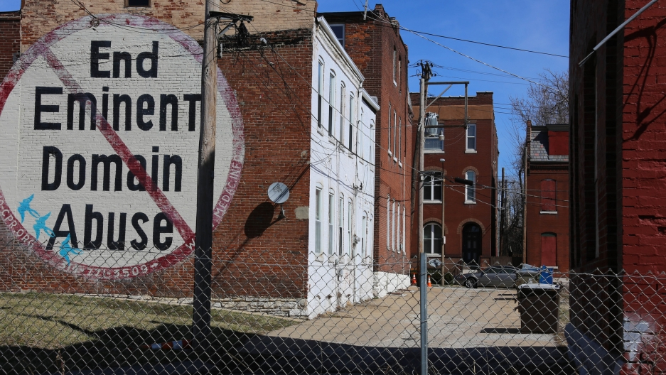 A brick building with hand-painted sign: End Eminent Domain Abuse