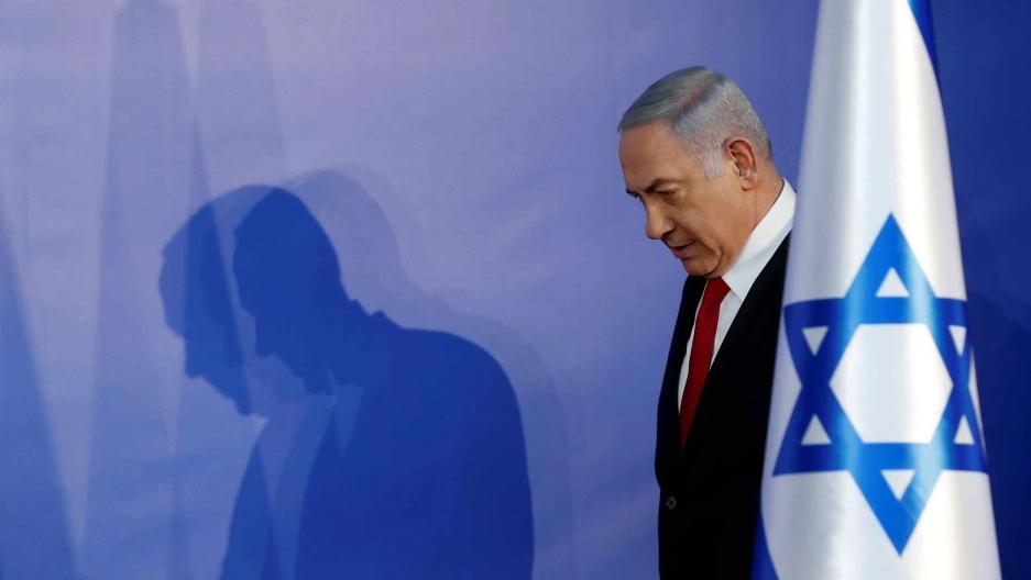 Benjamin Netanyahu stands behind an Israeli flag
