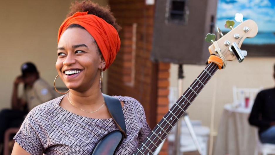 A woman wearing a colorful headband holds a bass guitar