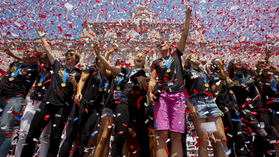 "A crowd of women stand under a shower of confetti. They have gold medals around their necks and are wearing matching shirts reading ""world champs."""