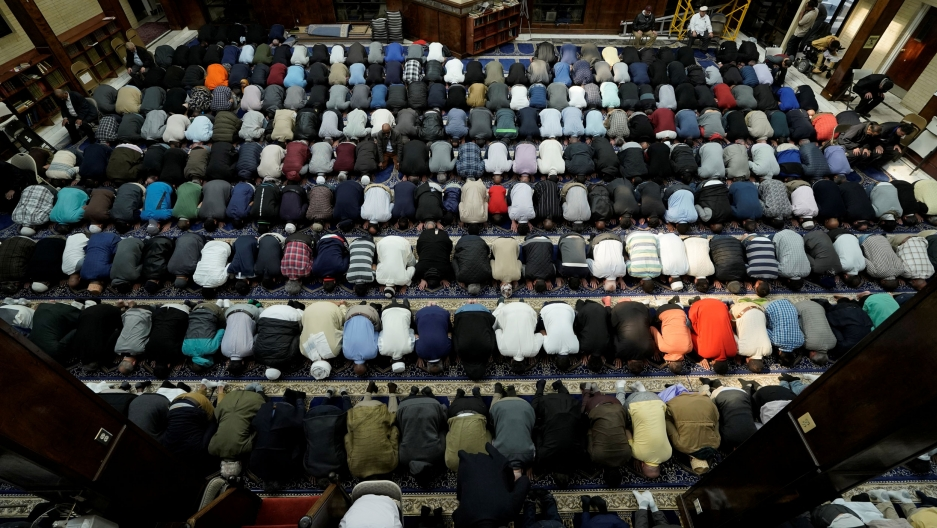 A photo taken overhead shows dozens of Muslims praying in a mosque