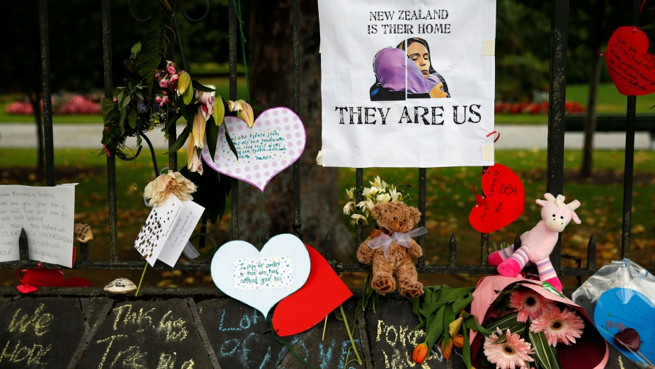 Flowers, cards and stuffed animals decorate a face as a tribute to victims of the Christchurch mosque shootings