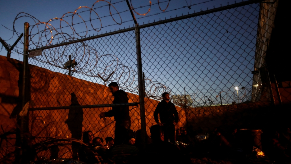 People a lit up by yellow streetlights as they sit inside a fenced area topped with razor wire as night falls