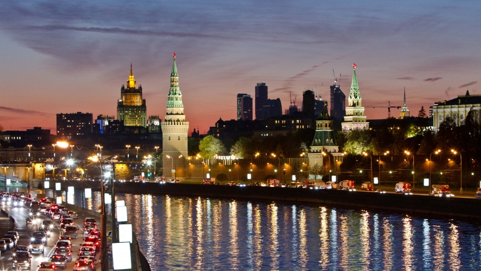An evening cityscape of Moscow with towers in the background and a river and traffic-filled road in the foreground