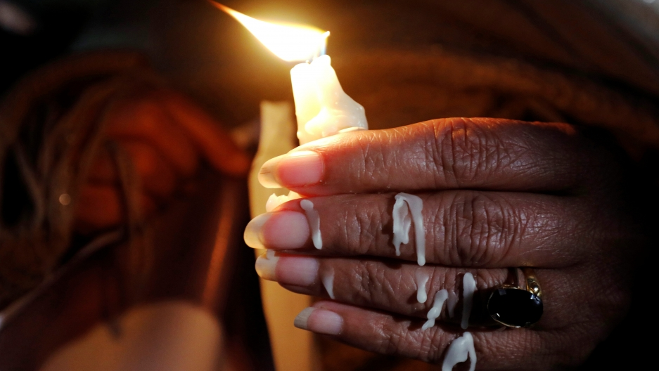 wax drips down a woman hand as she holds a candle