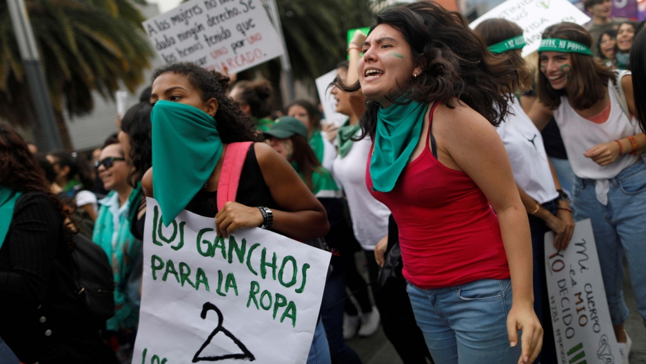 Women with green bandanas protest in a crowd