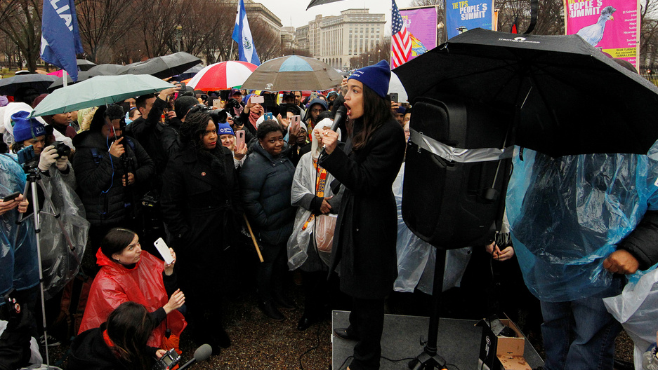 A woman with a microphone addresses the crowd surrounding her in the rain.