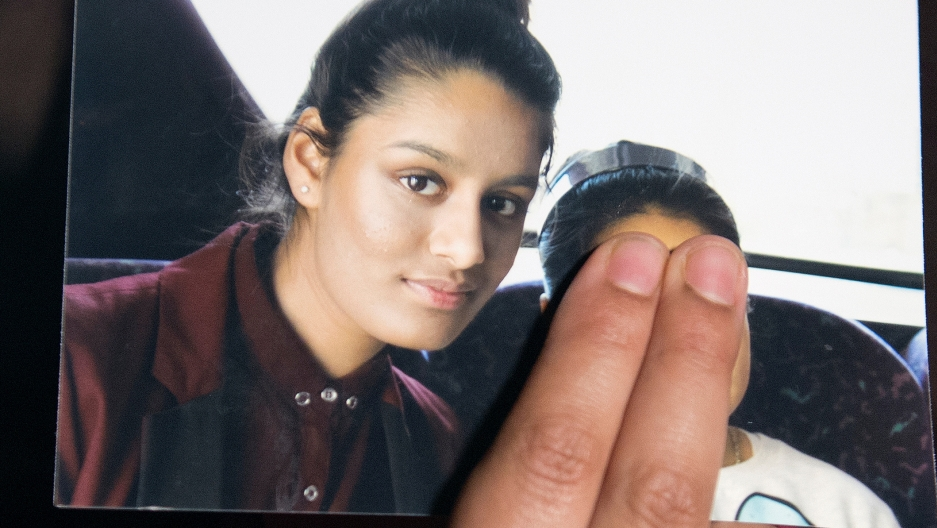 A girl holds a photo with her thumb over a face.