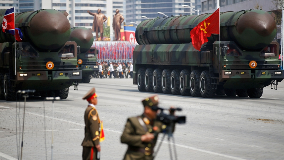 Intercontinental ballistic missiles are shown atop eight-wheeled camoflaged trucks being driven down a street.