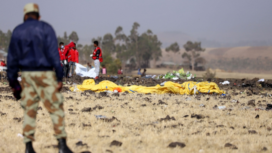 Members of the search and rescue mission are shown on the scene of the Ethiopian Airlines Flight ET 302 plane crash with a large yellow object in the middle of the photo.