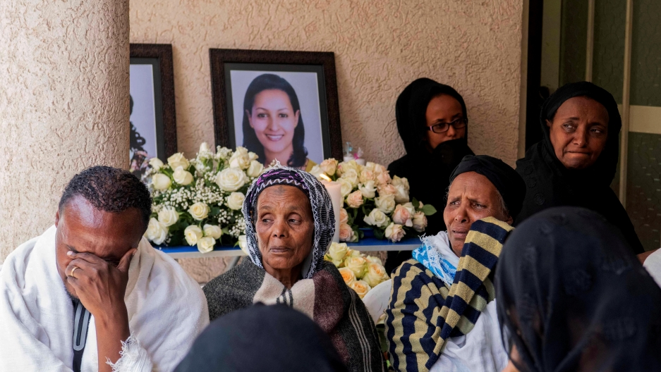 cloaked family members grieve over the deaths of those pictured behind them