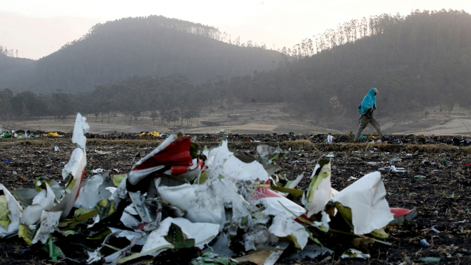 Debris from the Ethiopian Airlines Flight ET 302 plane crash is seen in the near ground of the photo with a man walking past in the background.