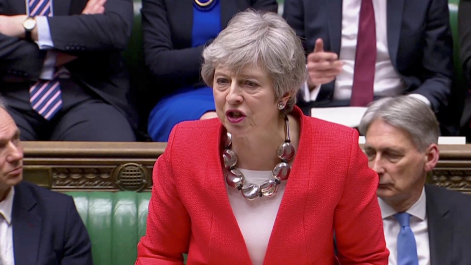 Theresa May in red suit in parliament.