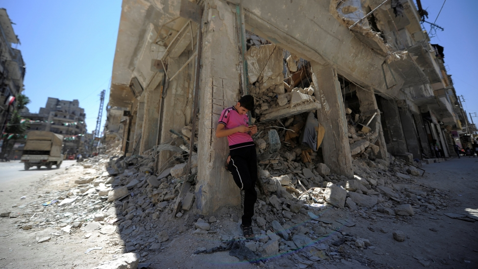 a man in a pink shirt leans against a building reduced to rubble