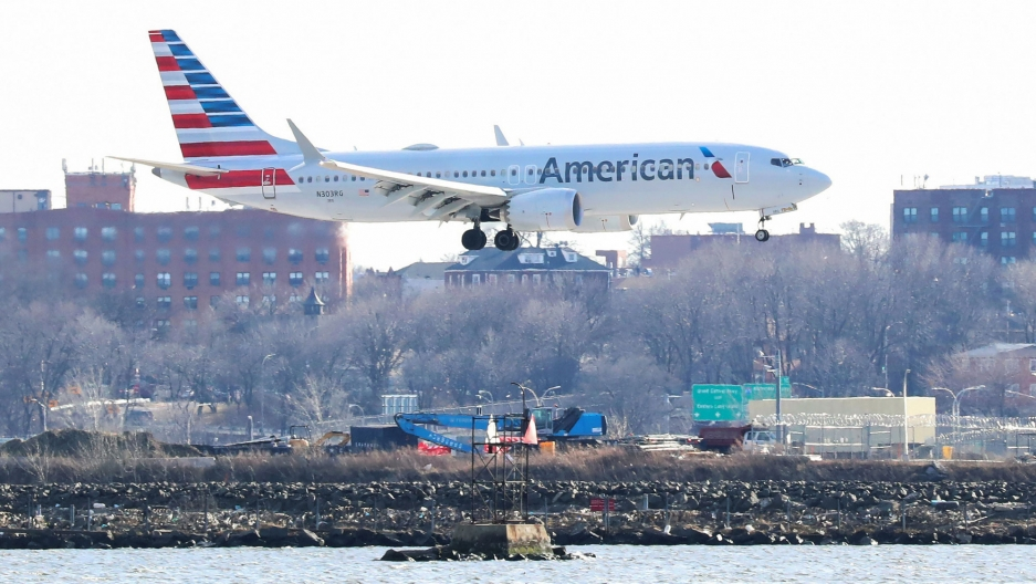 An American Airlines Boeing 737 Max 8 is shown flying from left to right in the photograph with several buildings in the background.