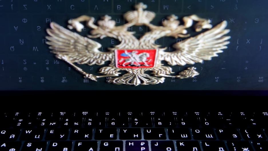The coat of arms of Russia is reflected in a laptop screen in this picture illustration