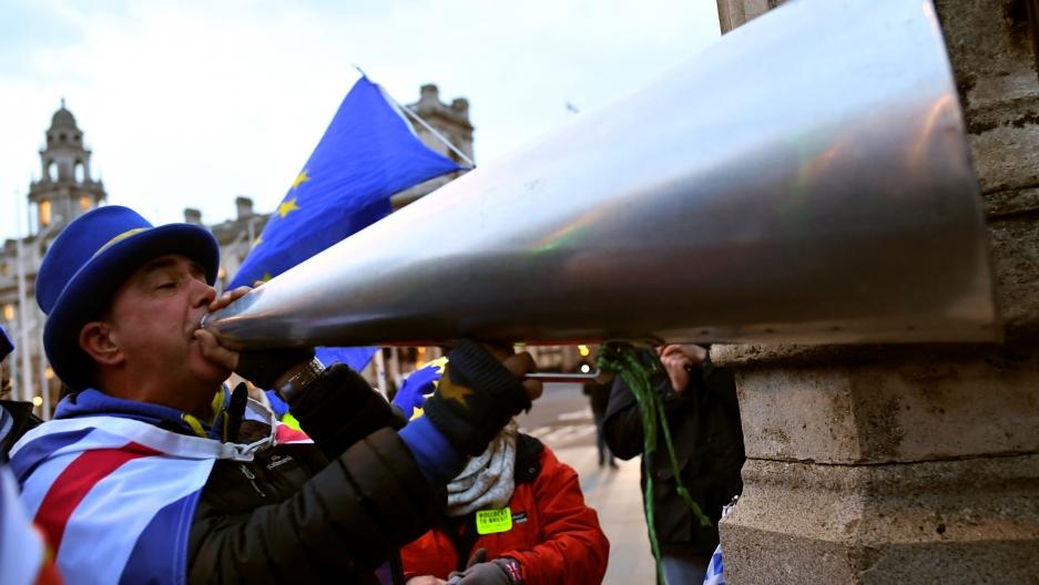 A man shouts into a silver megaphone.