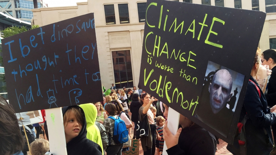 "Protesters are shown with placards that read, ""Climate change is worse then Voldemort."""