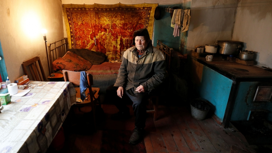 Vitaliy Kudla is shown wearing a two-tone jacket and hat while sitting in a small room with a bed behind him.