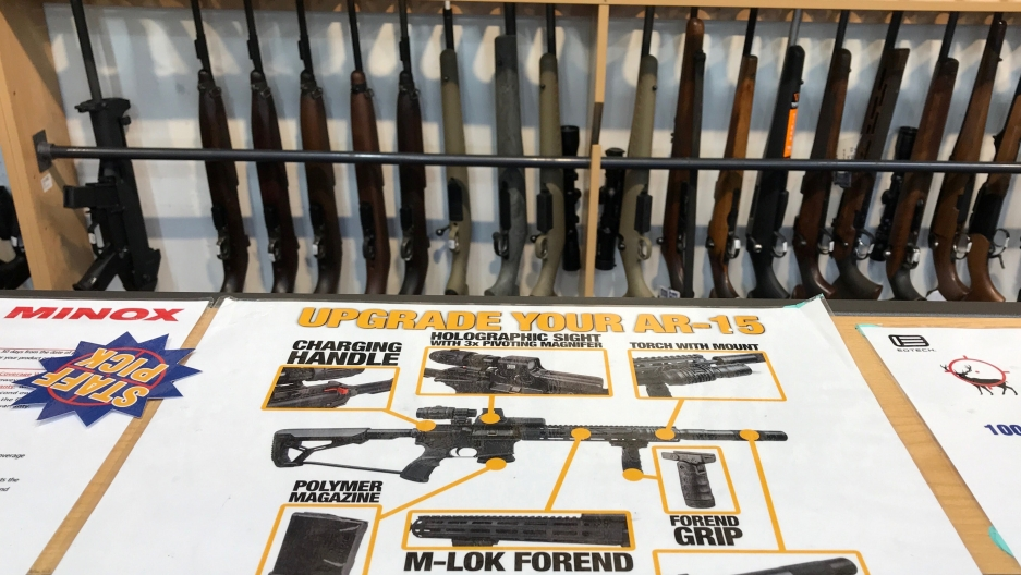 guns lined up by an advertisement for AR 15