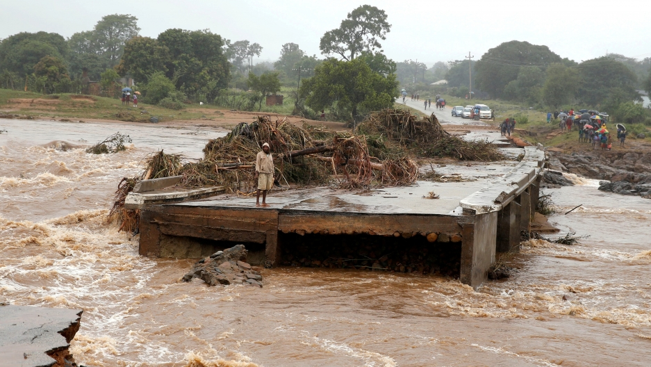 A man looks at a washed away bridge, surrounded by muddy water, along Umvumvu river