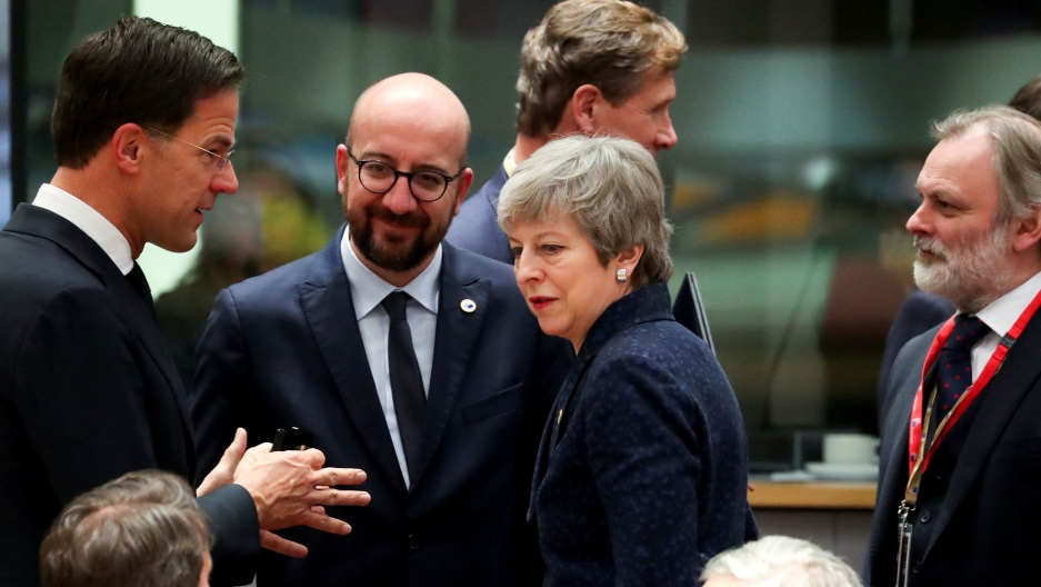 Britain's Prime Minister Theresa May is shown in the middle of a group of three men, all wearing dark suits.
