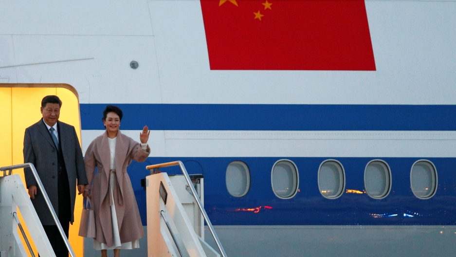 Xi Jinping and his wife step down from an airplane and wave.