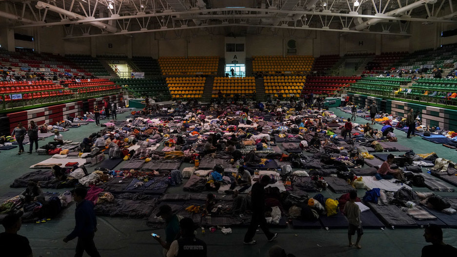 Migrants sitting and laying on mats are shown spread across a high school gymnasium floor.