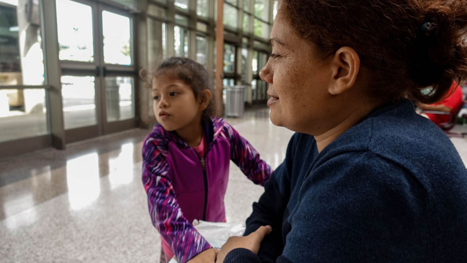 A close-up photo of a mother and her daughter, who is wearing pink, at a bus station.
