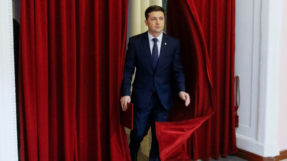 Actor Volodymyr Zelenskiy is shown in a blue suit walking out from parting red curtains.