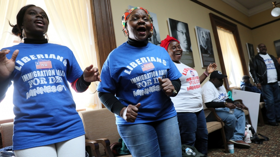 Women in blue and white shirts dance and sing.