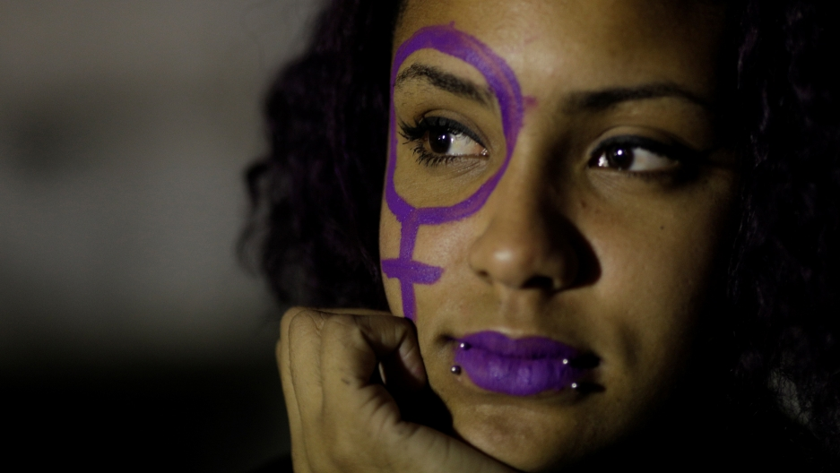 a close up of an abortion rights activist with purple paint on her face