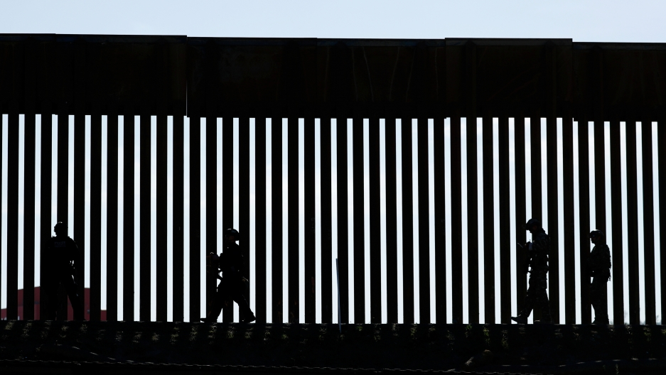 Shadow of patrolmen along slated wall at US border.