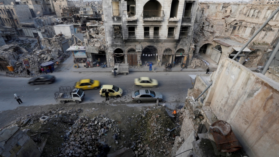 Destroyed buildings, cars, and people and are seen from across the street in Aleppo's old town.