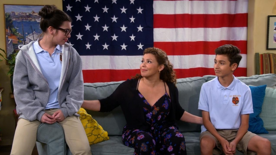 A woman and a boy sit on a couch, a girl sits on the couch arm. Behind them, an American flag.