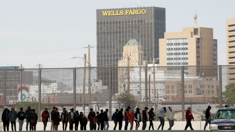 "A line of people stand along a fence. Behind them, a high rise office tower reads ""Wells Fargo"""