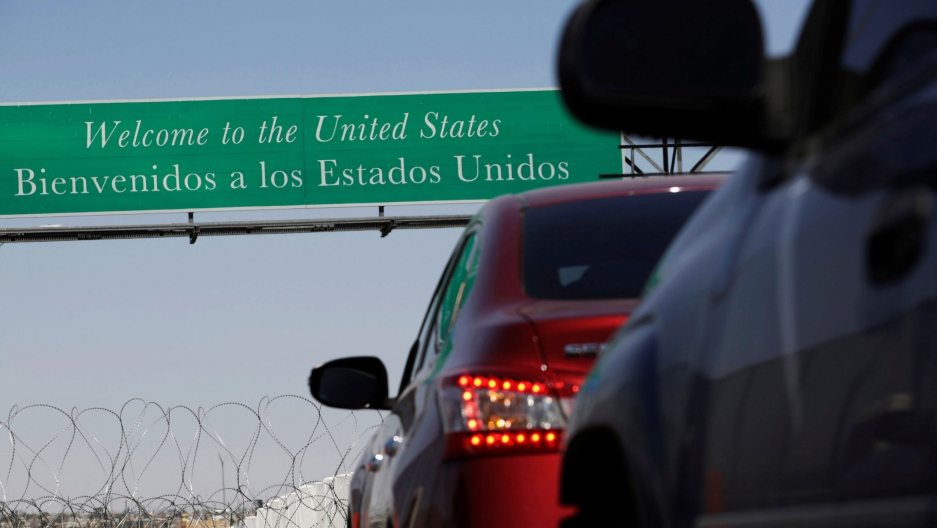 "A sign says ""Welcome to the United States"" as cars line up underneath it"