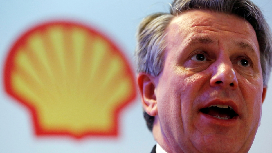A man speaks with a Shell oil yellow shell logo behind him