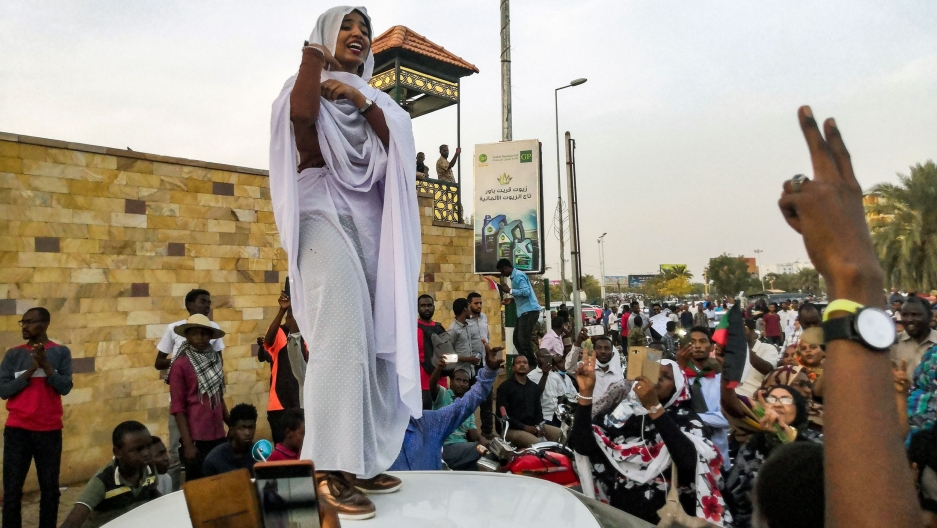A woman stands atop a car and speaks to a crowd