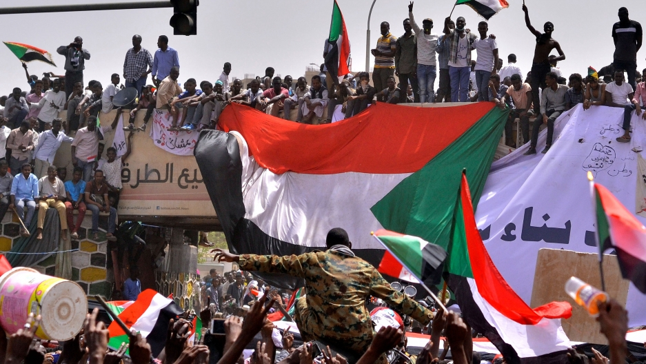 A thick crowd of people wave Sudanese flags and celebrate. A man in military fatigues is being carried through the crowd.