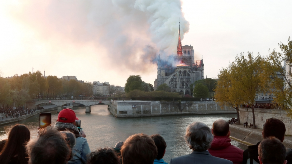 a crowd of people watch as the notre dame cathedral billows smoke in the distance