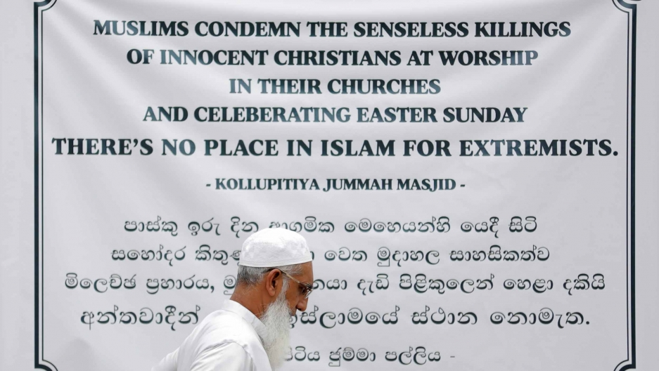 "A man walks by a large banner that reads ""Muslims condemn the senseless killings of innocent Christians at worship in their churches and celebrating Easter Sunday. There's no place in Islam for extremists."""