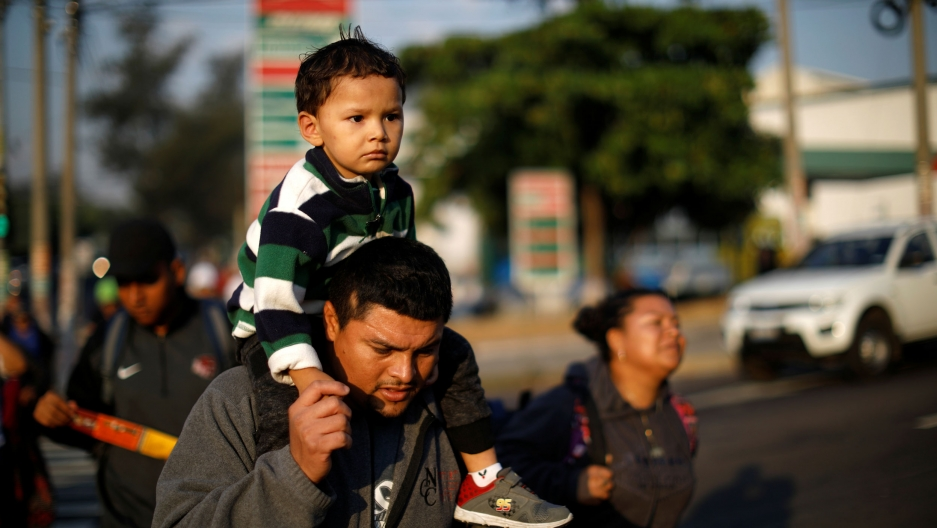 A father is shown holding his son on his sholders as they walk in a caravan of migrants en route to the United States.