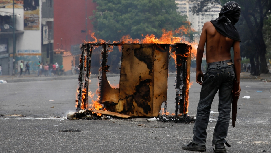 A demonstrator stands shirtless nex to a mostly burned rectangular frame during a protest .